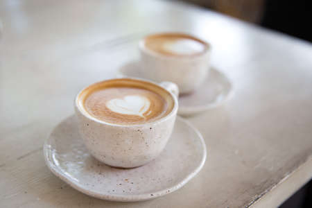 Two Cups of hot cappuccino on white wooden table background. Place for text. Top view.