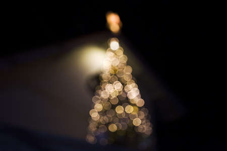 Christmas tree blurred lights closed to house. Festive concept.