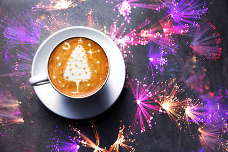 Tasty cappuccino with Christmas tree latte art on gray concrete background. Holiday concept.