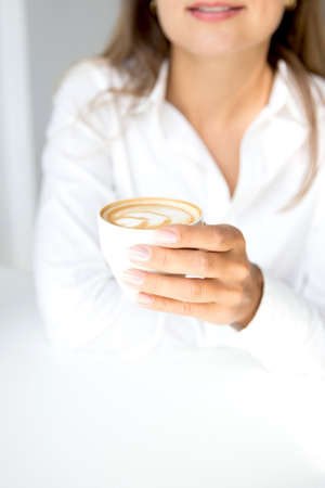 Woman in white shirt is holding cup of cappuccino coffee in day time, it is tender hand