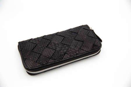 Deep black snakeskin wallet purse isolated on a white background. Fashion concept. 스톡 콘텐츠