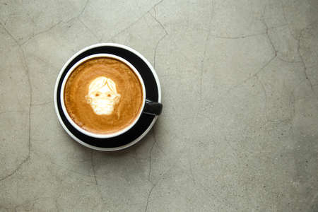 Cappuccino with latte art man in facial mask on gray concrete background. Heathy protection concept. Place for text.