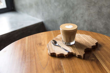 Glass of tasty latter with love art on the wooden table and textured desk. Morning concept.