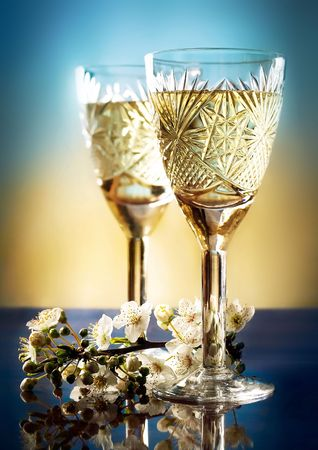 romantic glasses with white wine and plums branch on blue Фото со стока