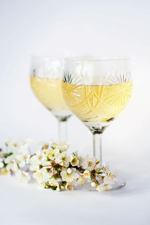 romantic glasses with white wine and plums branch