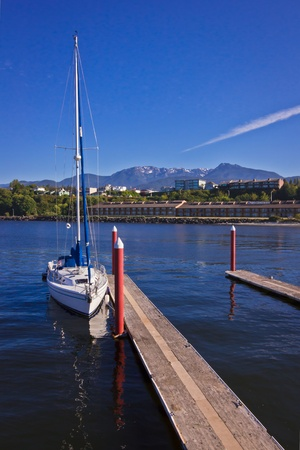 A Sailing Boat with Mountains and Water Фото со стока