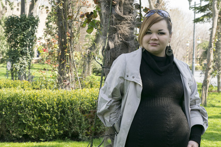swelling: pregnant woman on a background of trees