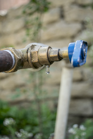 water dripping: a drop of water dripping from the tap