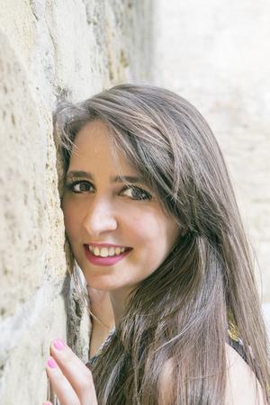 color model: Brunette girl leaned against a stone wall