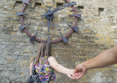pull along: the girl pulls the hand of the guy in the background of the large clock on the stone wall Stock Photo