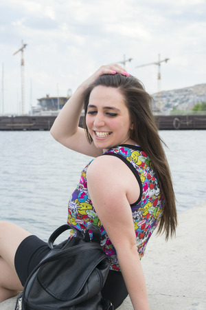 brunette girl sits on the waterfront