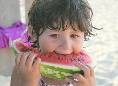 niños sanos: brunette girl 3 years eats a slice of watermelon outdoors