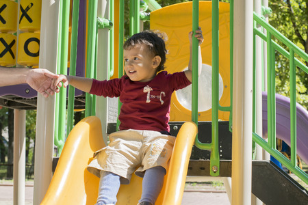 hyperactivity: the parent holds the hand of a child who is sitting on the slide and going down Stock Photo