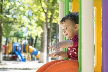 playground equipment: dark-haired boy of 2 years playing on the Playground outdoors