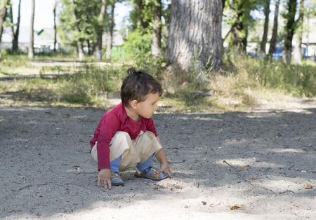 en cuclillas: morena niño 2 años en cuclillas en la arena en el Parque