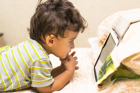 two visions: the boy looks at the iPad on the bed