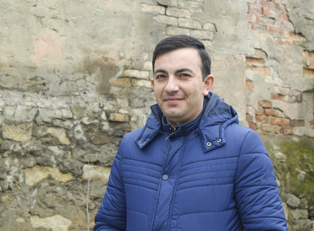 village man: village man stands in a stone wall in the jacket Stock Photo