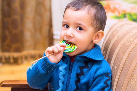 boy kid: little boy eating candy on a stick