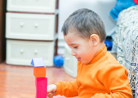 3 persons only: boy 2 years builds a tower of blocks Stock Photo