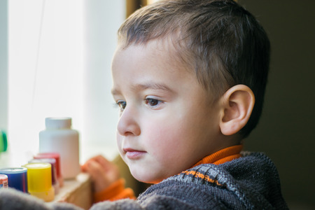 autism: little boy looking out the window