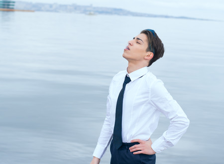 stylish teen in a shirt and tie smokes on the background of the sea