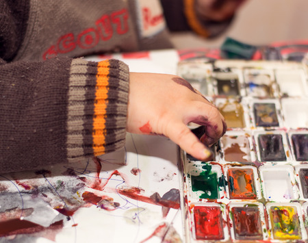 manos sucias: the boy paints with watercolors on paper, dirty hands