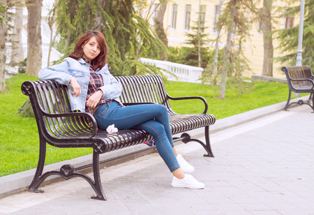 calm woman: young beautiful woman sitting on a bench in the Park