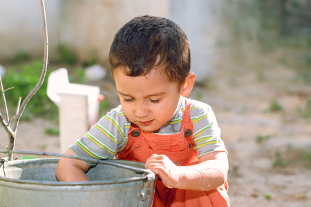 a boy plays with a bucket of water