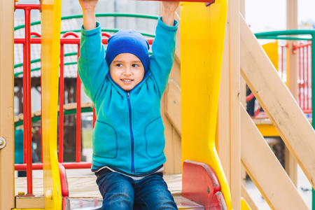 boy plays on the Playground in the spring
