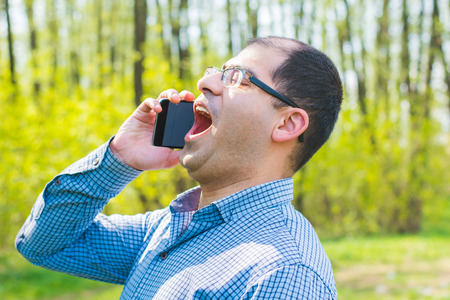 man excitedly talking on the phone outdoors