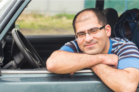 male driver sitting in the car and smiling