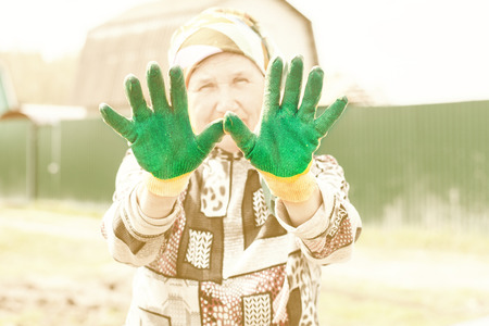 elderly woman with gloves on the garden. toned.