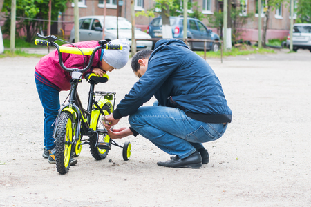 father and son repairing a childs Bicycle