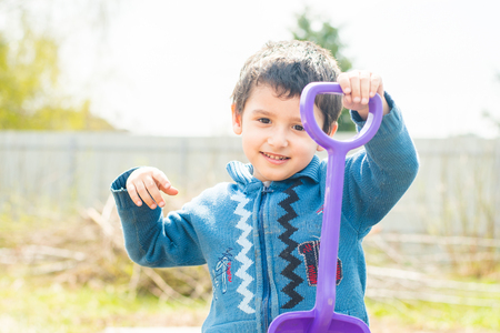 boy 4 years old with a baby shovel outdoors Stock Photo