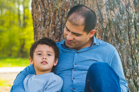 father and son sit under a big tree