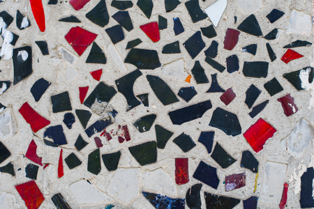texture of the wall. broken glass pieces of blue and red in the concrete wall