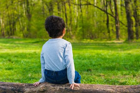 dark-haired boy sitting on a log alone Stock Photo