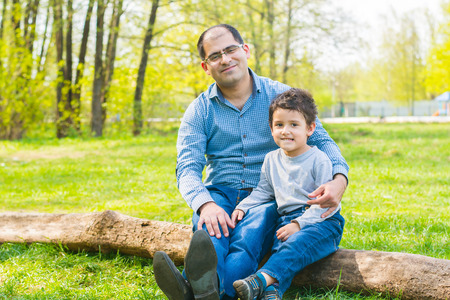 dad and son sitting on a log in the meadow