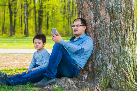 father and son sitting under a tree in the summer. Father is busy with the phone