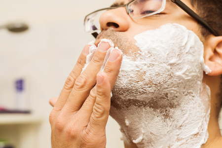 man in glasses Caucasian nationality shaves his face