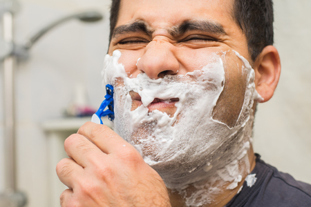 middle-aged man shaves his face in the bathroom