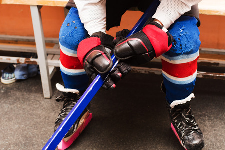 legs of a hockey player sitting on the bench Stock Photo
