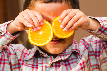 boy with orange slices in his hands Stock Photo
