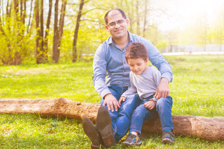 dad and son sitting on a log in the meadow. toned