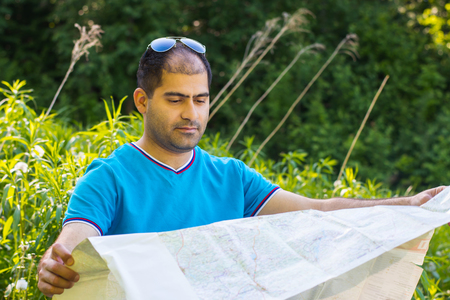Middle-aged man brunette with a map in the forest