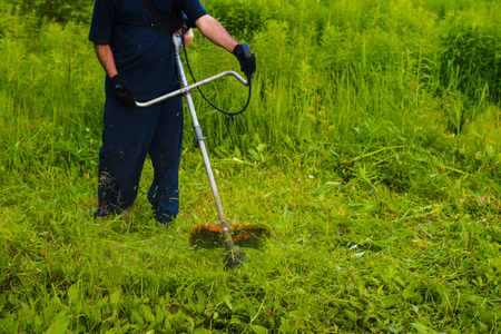 Man with a manual lawn mower mows the grass Stock Photo