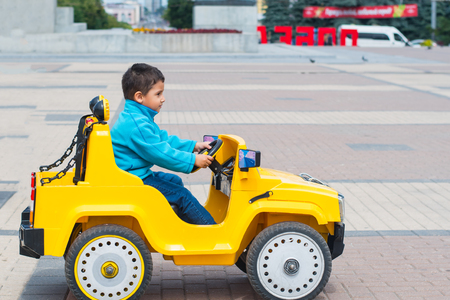 brunette boy rides an electric yellow car in the Park Stock Photo