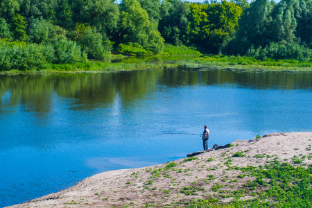 alone fisherman on the river Bank fishing in the day in summer Banco de Imagens