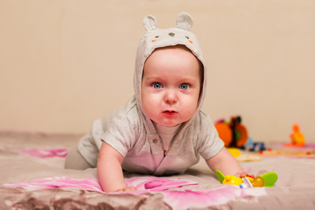 charming baby with blue eyes trying to crawl