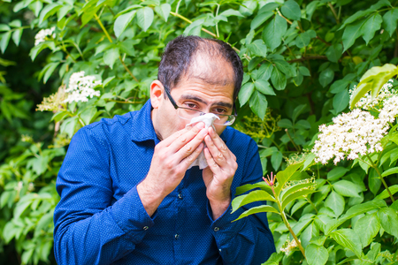 a middle-aged man near a tree with flowers, he is allergic to pollen Stock Photo